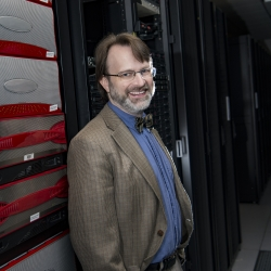Jeremy Kepner poses with LLSC server stacks.