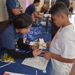 A Laboratory volunteer helps a student to construct a lightsaber.