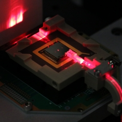 A square electronic chip with a red laser hitting the side of it