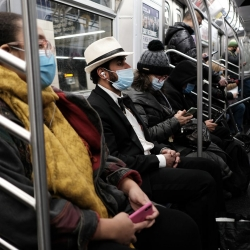 An image of riders on a subway train