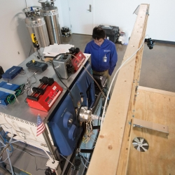 Researchers conducted vapor measurements in situ with canines. The canines walked up onto the wooden platform to smell a training object while the mass spectrometer validated the presence of trace explosive vapors on the object.