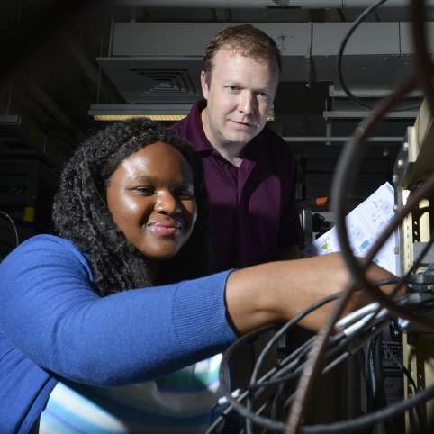 Derrick Feld looks on as AFCEA intern Chi-chi Nwodoh connects wires on the test terminal she helped build.