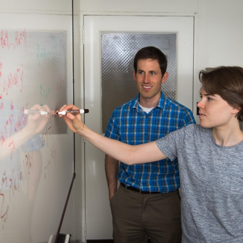 As mentor Henry Romero looks on, UROP student Gabriela Studt does calculations to compare soft-decision decoding algorithms for Reed-Solomon error-correcting codes.