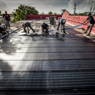 All hands are on deck as the team adheres the solar modules onto the roof of the Boys and Girls Club. Photo: Lorenzo Moscia