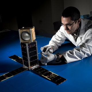 Mike DiLiberto leanes next to the MicroMAS-2A cubesat.