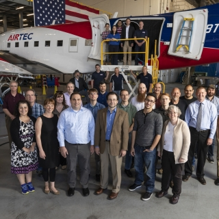 A group of about 30 people pose in front of an airplane