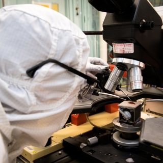A researcher measures a battery performance while looking through a microscope.