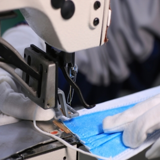 An image of a person (only their hands are shown) using a sewing machine to sew a blue surgical mask.