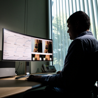 A man sits at an office desk looking at a large monitor. the left hand side shows data graphs, the right side shows two images of the back of a woman's arm with a crown tattoo, and a green box around the tattoo.
