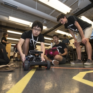 Students in the Beaver Works Summer Institute practice steering their self-programmed robotic racecars, a challenge that included using the robots' sensors, programmed to detect a lane marking.