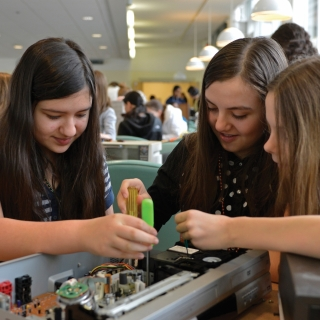 "Our ""Wow! That's Engineering!"" workshop for girls offers a reverse engineering station where the girls disassemble a variety of electronics to see how the parts of a machine are connected."