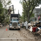 A photo of a large truck picking up debris lining a street