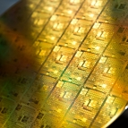 A photo of gold-colored integrated circuit wafer.