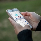 "Two hands hold an Iphone; the screen shows the interface of a COVID-monitoring app that reads ""No significant exposures"""
